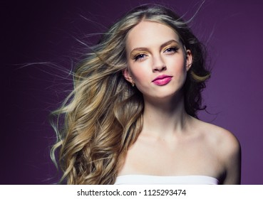 Beautiful female with blonde long curly hair over purply background