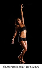 Beautiful female body of athlete on a dark background