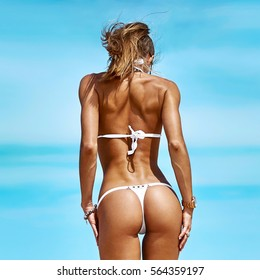 Beautiful female body. Back view of perfect woman's figure in lingerie over blue sky