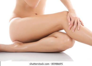 Beautiful female body isolated over white background. Sitting on the floor touch leg by hand, Beauty and skin care concept.