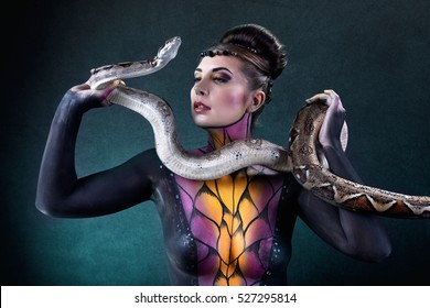Beautiful female body painted as a snake goddess with Burmese Python snake