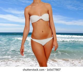 Beautiful female body with white bikini in the beach
