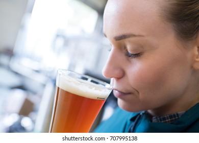 beautiful female brewer testing beer at bewery