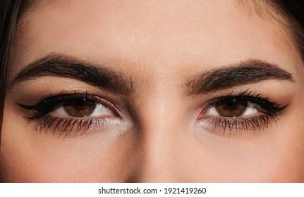 Beautiful female Brown eyes with long eyelashes, elegant makeup, closeup