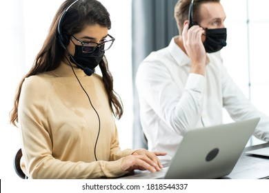 Beautiful female call center operator working on computer in office. Communication support for callcenter and customer service Helpdesk.Worker wearing face mask prevent covid-19 virus