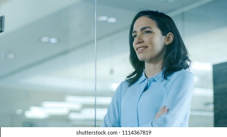 Beautiful Female CEO in Her Office Looks out of the Window. Strong Independent Woman with Big Accomplishments Behind and Ahead of Her.