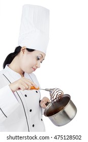 Beautiful female chef cooking chocolate with a pan while wearing uniform, isolated on white background