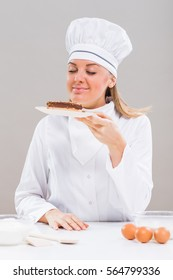 Beautiful female chef has made delicious cake and she is smelling it.Female confectioner smelling slice of cake