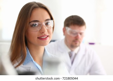 Beautiful female chemist doctor portrait goggles in laboratory smiling and looking at camera. A group of people working on the creation of a new cancer drug in the hospital are analyzing the materials