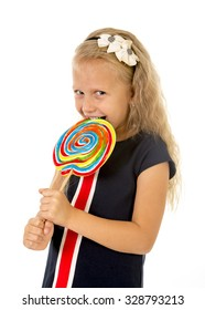 beautiful female child with long blond hair and blue eyes holding huge spiral lollipop candy smiling happy and excited eating and licking isolated on white background in sugar and sweet concept