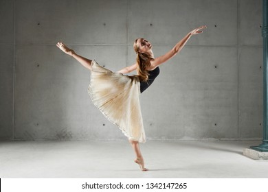 Beautiful female classical ballet dancer lifting leg effortless on stage with harmony, body shape movement, fitness flexibility indoors. Woman performing arts, balance strength concept, lifestyle.