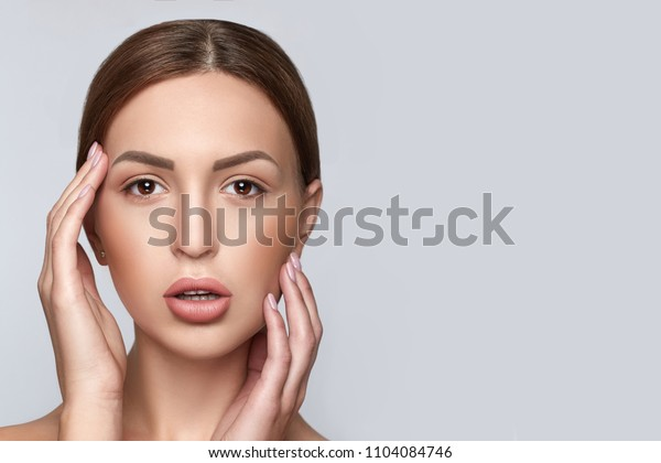 Beautiful female with clean clear skin, natural make-up, and white teeth on grey background. Beauty and spa concept. Healthy skin. Horizontal