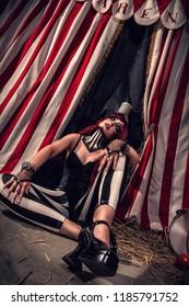 Beautiful female clown sits on floor somewhere on scene of dark circus arena