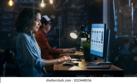 Beautiful Female Coder Works at Her Desktop on Her Peropnal Computer. Her Male Colleague Sits Next To Her. Evening Office Has Creative Lighting.