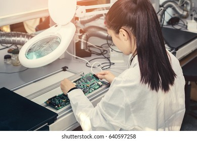 Beautiful female computer expert professional technician examining board computer in a laboratory in a factory. Troubleshooting. Technical support. Engineering. Manufacturing.