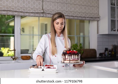 Beautiful female confectioner in chefs uniform standing in a modern kitchen, decorating a naked chocolate and strawberries cake with berries and macaroons