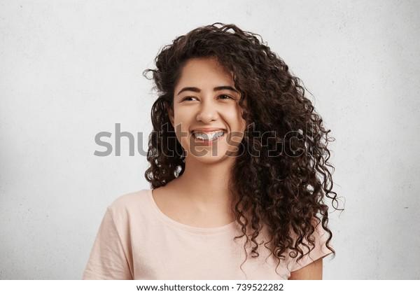 Linda fêmea com cabelos crespos encaracolados, nacionalidade mista, vestida casualmente, sorri amplamente, mostra dentes brancos perfeitos, sendo feliz em receber elogios do namorado, isolado sobre fundo branco