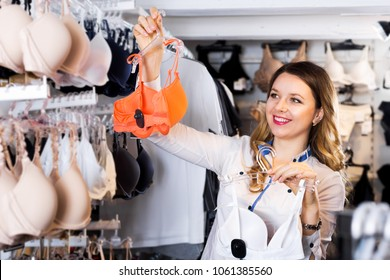 Beautiful female customer deciding on pretty bra in underwear shop