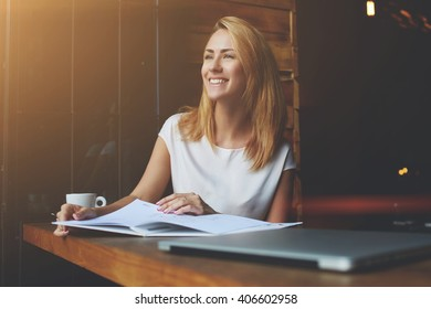Beautiful female with cute smile looking away while relaxing after work on her laptop computer, charming happy woman enjoying rest and good day while sitting alone in modern coffee shop interior