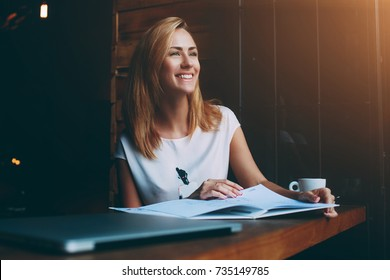 Beautiful female with cute smile is looking away while relaxing after work on her laptop computer, charming happy woman enjoying rest and good day while sitting alone in modern coffee shop interior