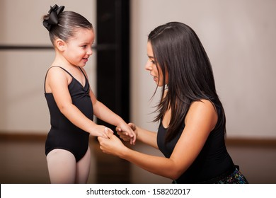 Beautiful female dance instructor talking to and coaching one of her students in a dance academy