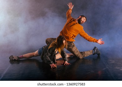 The beautiful female dancer is laying on the floor while her male partner performs an exotics unique modern art moves over her.