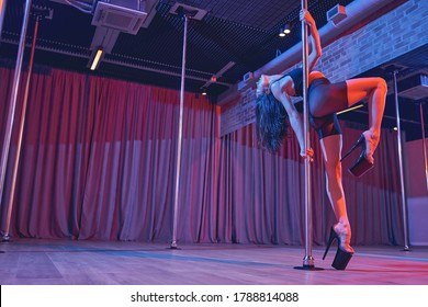 Beautiful female dancer wearing sexy high heels and black shorts while dancing on pylon in studio with dim neon lighting