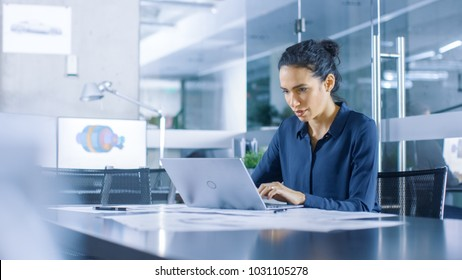 Beautiful Female Data Analyst sitting at the Table Works on a Laptop. Stylish Woman in the Modern Office Environment.