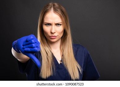 Beautiful female dentist wearing scrubs showing thumb down on black background with copyspace advertising area