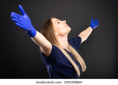 Beautiful female dentist wearing scrubs making winner gesture with arms spread on black background