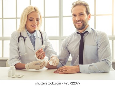Beautiful female doctor is bandaging man's injured hand. Patient is looking at camera and smiling while sitting in doctor's office