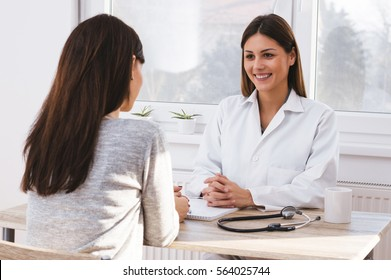 Beautiful female doctor consulting patient