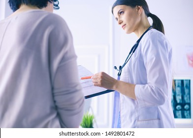 Beautiful female doctor explaining medical treatment to a patient