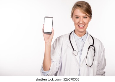 Beautiful female doctor smiling and showing a blank smart phone screen isolated on a white background. Portrait of happy female doctor promoting smart phone.