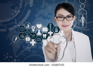 Beautiful female doctor with stethoscope on blue background