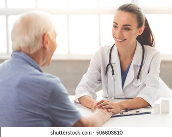 Beautiful female doctor in white medical coat is consulting her patient, holding his hand and smiling while sitting in office