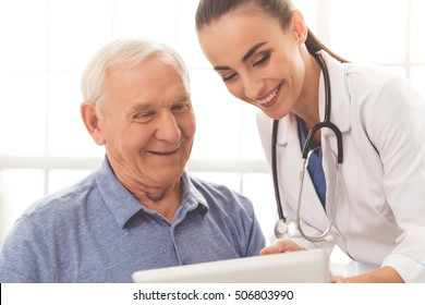 Beautiful female doctor in white medical coat is consulting her handsome old patient, using a digital tablet and smiling