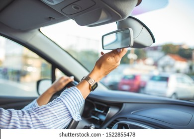 Beautiful female Driver adjusting the Rear Mirror. Women are adjusting the rearview mirror of the car. Hand adjusting rear view mirror. Safety concept.