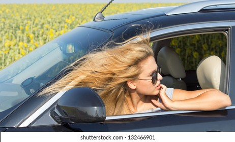 Beautiful female driver in car looking back with her head out of the window and her blonde hair blowing in the wind