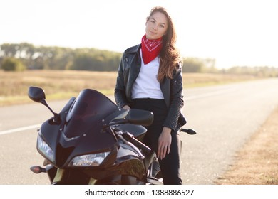 Beautiful female driver sits on black fast motobike, dressed leather jacket and red bandana, travels around country by motobike, stops on side of road to have rest, looks directly at camera.