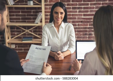 Beautiful female employee in suit is smiling during the job interview