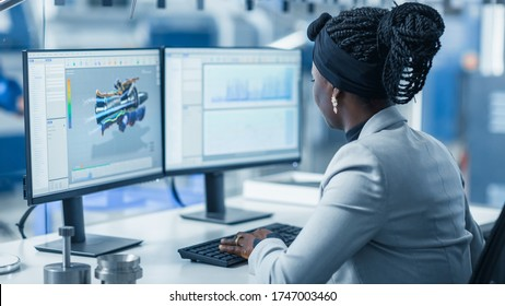 Beautiful Female Engineer Working on Personal Computer in the High-Tech Industrial Factory, She Uses CAD Software Designing 3D Turbine. Over the Shoulder Shot.