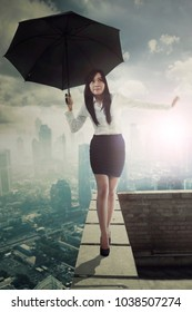 Beautiful female entrepreneur holding an umbrella while walking on the rooftop