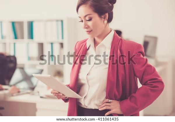 Beautiful female entrepreneur reading information on digital tablet