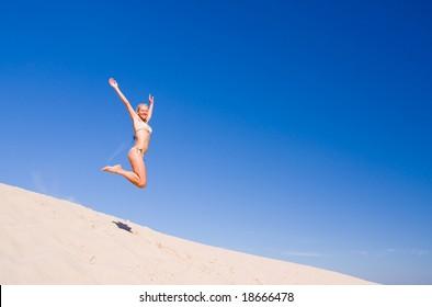 beautiful female exercising on the sand dunes