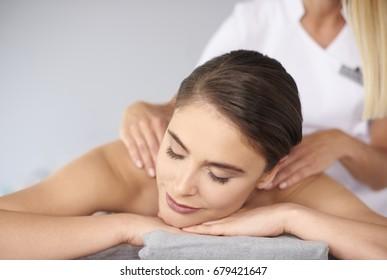 Beautiful female with eyes closed during back massage