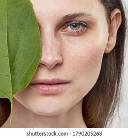 Schönes weibliches Gesicht mit gesunder Haut und grüner Pflanze