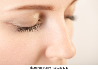 beautiful female face with a natural beauty makeup look eyelashes closeup on a white background