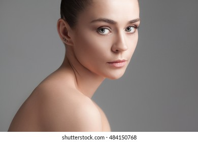 The beautiful female face. The perfect and clean skin of face on gray