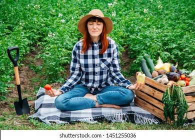 Beautiful female farmer meditating while sitting on a blanket near fresh organic vegetables in a wooden box against the background of a vegetable garden